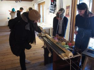 Audrey and Afroditi guide a Social go-er on how to Knit Ur Face using a hacked knitting machine