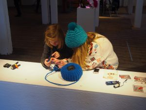Sam shows off a sonified knitting project to a curious kid.